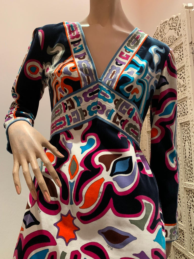 A wonderful 1960s Emilio Pucci silk jersey knee-length dress in classic Pucci colorful print, V-neck line, Empire waist, and long sleeves. Side and back zipper.