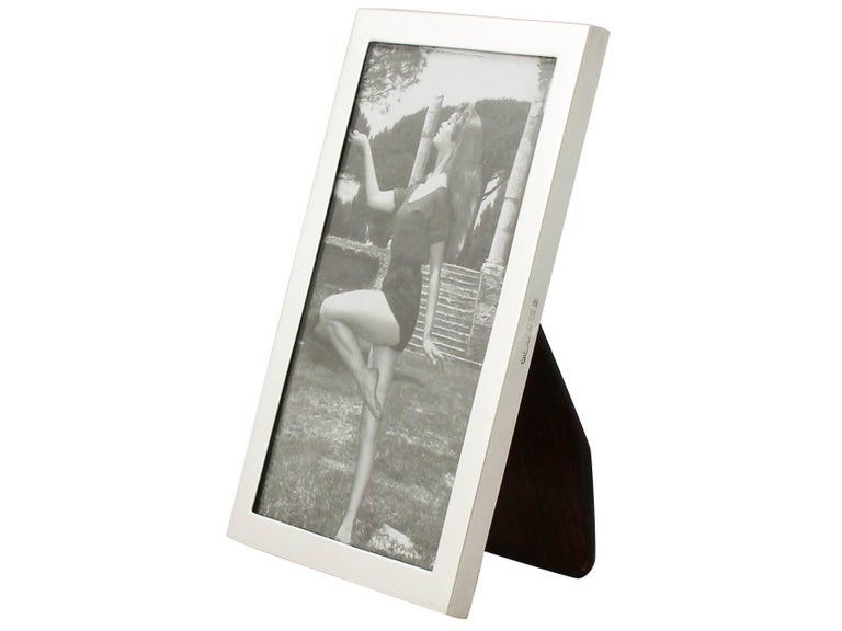 An exceptional, fine and impressive vintage Elizabeth II English sterling silver photograph frame; an addition to our ornamental silverware collection.  This exceptional vintage Elizabeth II sterling silver photo frame has a plain rectangular