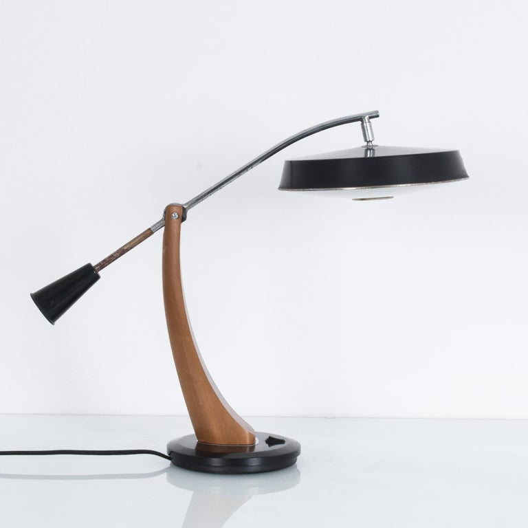 A pendulum desk lamp made by Spanish designers Fase President. A curved wooden arm with a counterpoised metal rod supports a black lacquered lampshade while allowing the bulb to be raised and lowered. The convex, gently frosted lower disc of the