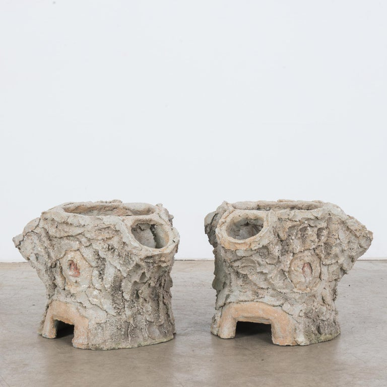 A pair of faux bois concrete planters from France, circa 1960. The form is organic, reminiscent of tree stumps. The rugged, textural application of concrete to the outer surface gives the impression of tree bark. Lively, rustic and nature-inspired,