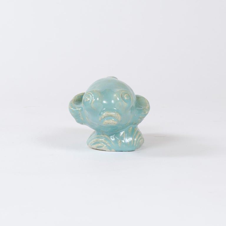 An uncommon white stoneware betta fish sculpture with thick glossy cyan glaze. Signed.