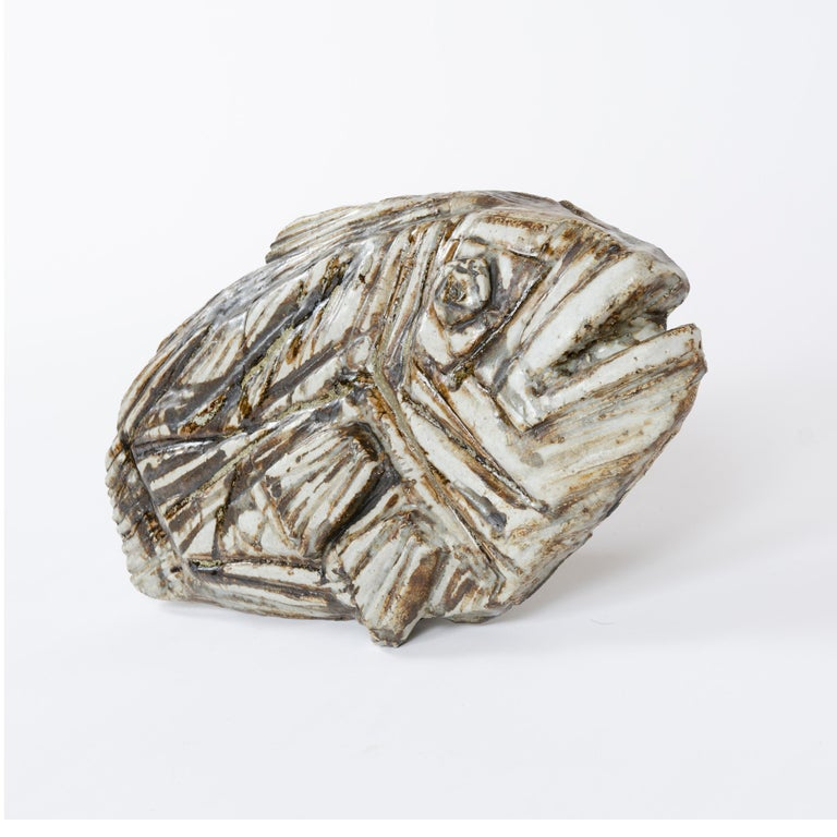 A substantial stoneware sculpture of a fossilized flatfish having a rich and variegated matte glaze over expressive textural impressions enriched by brown underglaze markings. Signed and stamped.