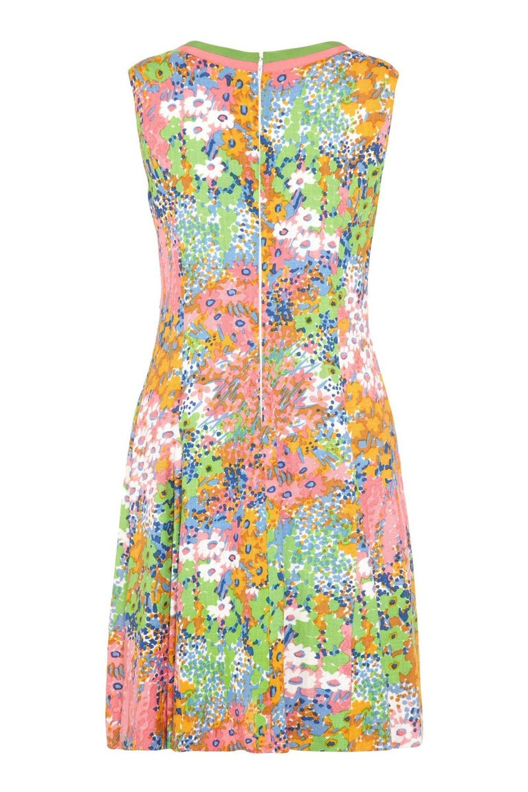 This pretty 1960s linen floral print shift dress has a fresh, buoyant aesthetic and is in lovely vintage condition. Featuring a V neckline trimmed in contrasting green and sugar pink grosgrain ribbon, the dress is sleeveless with a central zip