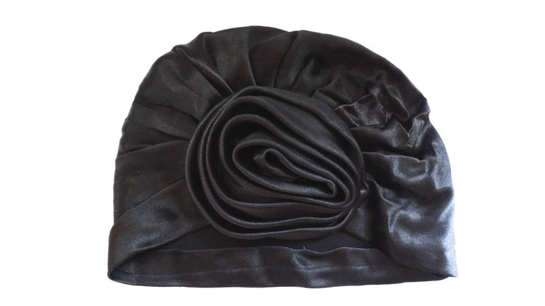 We love a good turban- and you will too with our adorable Frank Olive hat circa the 1960s! Black satin fabric, classic turban construction with gathered three dimensional rose effect at the front. Pulls onto the head effortlessly- no tying required!