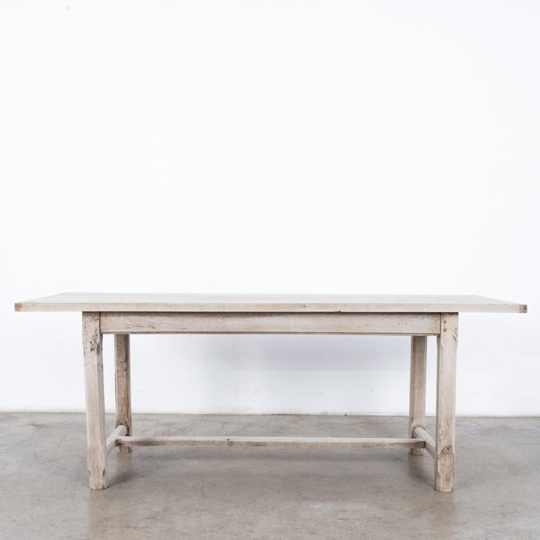A bleached oak dining table from France, circa 1960. A rectangular tabletop sits atop four legs, joined with a slender strut. The chamfered table legs lend a lithe, decorative touch. The bleached finish of the restored wood emphasizes the lightness
