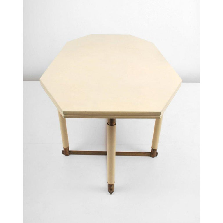 This fine octagonal table by Maison Jansen originates from France in the 1960s and could be used as a dining table or desk. Its off-white leather octagonal tabletop offers ample space for any occasion and its brass base and leg accents add a