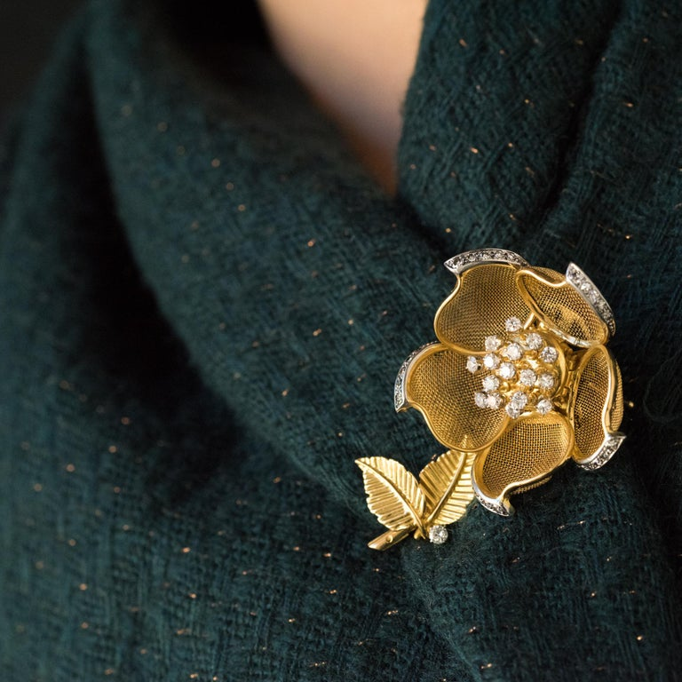 Brooch in 18 karats yellow gold, mercury head hallmark and platinum, young girl's head hallmark. Representing a rose, this vintage brooch is articulated and can thus present the flower open or closed in bud. The pistils are formed of movable golden