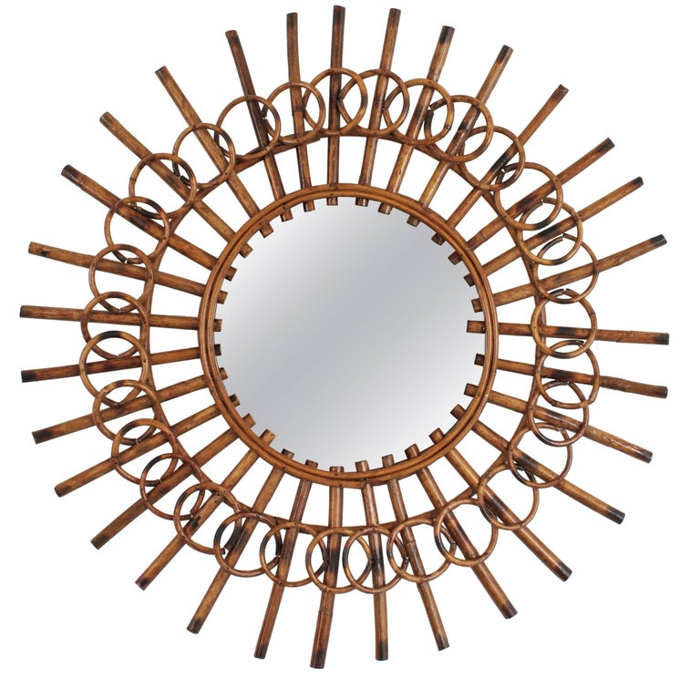A highly decorative rattan sunburst mirror framed by circles with a lovely color. This mirror has the French Riviera Mediterranean taste with an unusual handcrafted beautiful work. Lovely to place it alone or in a wall decoration with other mirrors