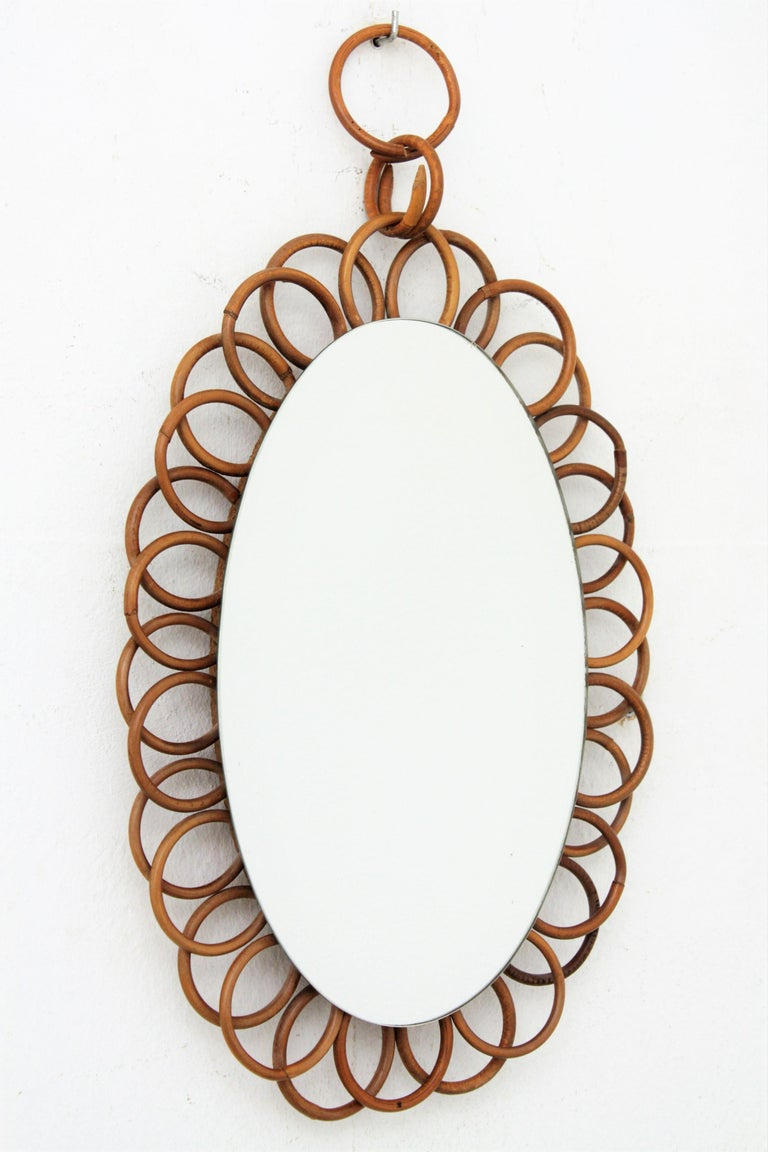 A lovely handcrafted rattan flower shaped rattan oval mirror hanging from a rattan chain. This piece has all the taste of the Mid-Century Modern Mediterranean taste, France, 1960s. Overall dimensions: 46cm H x 26.5cm W // Glass dimensions: 29.5 cm