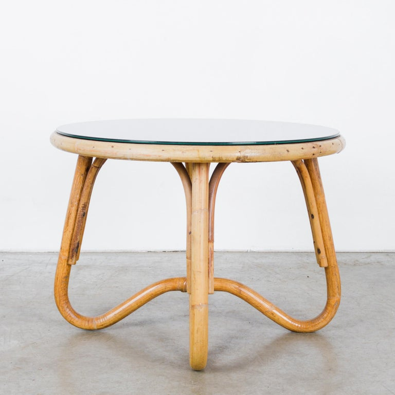 A round bamboo table with a black glass top from France, circa 1960. The supple shape makes inspired use of the natural pliability of bamboo; the legs loop and unite beneath the center of the tabletop, giving a Mobius effect of an unbroken line. The