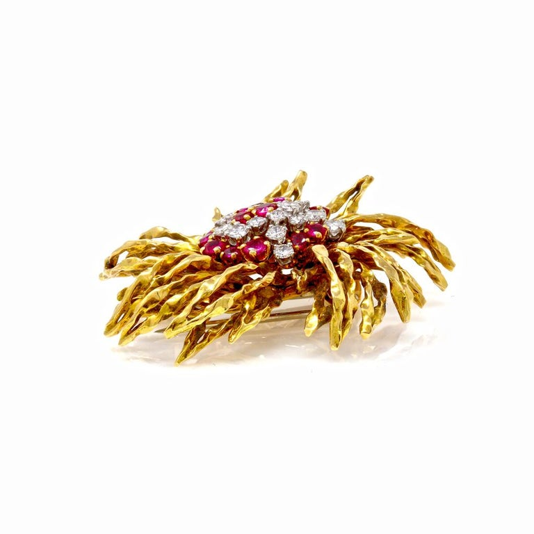 18 karat yellow gold, ruby and diamond brooch, French, circa 1960, of stylized floral design set in the center with round diamonds weighing approximately 1.50 carats, and round rubies weighing approximately 1.55 carats, gross weight 28.4 grams,