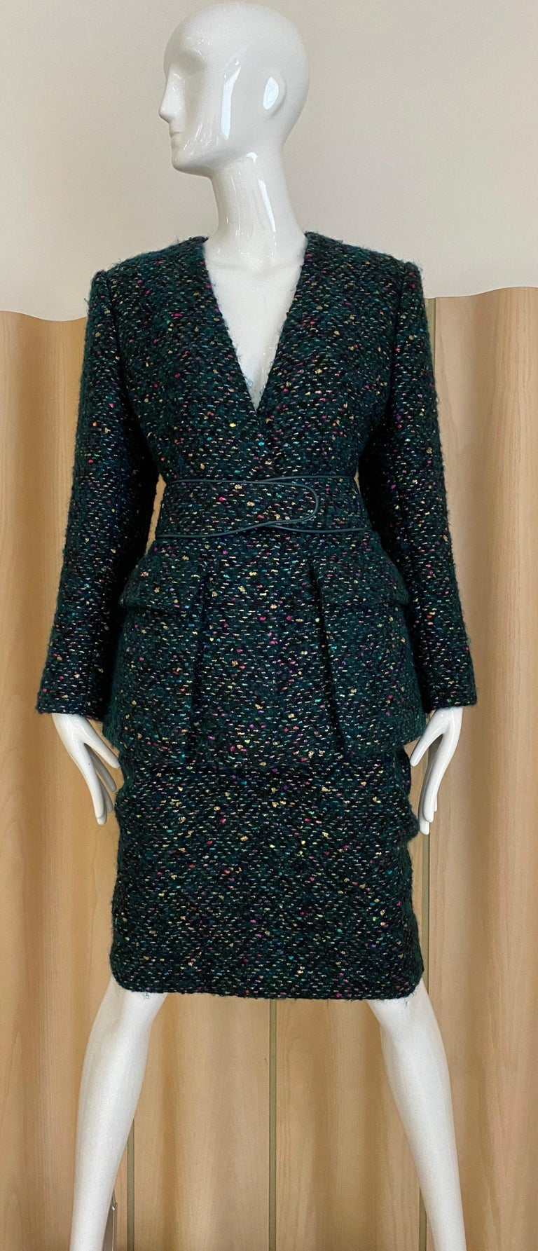 Vintage Galanos Skirt Suit from the 1960's in a cashmere and wool boucle with metallic threads woven into it. Jacket has a v neck no collar, one center button, two flap patch pockets and a contoured belt trimmed in leather and metal fasteners. Knee