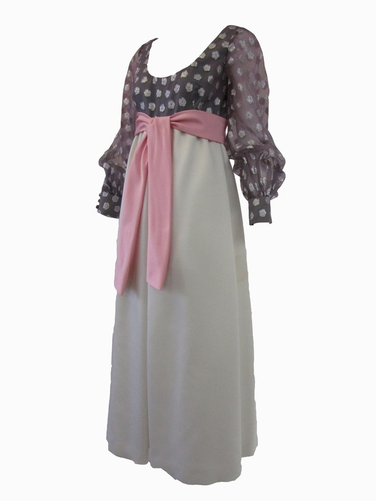 Youthful & fun scoop neck evening gown done in a sheer metallic polka dot over silk with a pink bow belt. Silk satin gathered skirt is an off white. Sheer sleeves button at cuff. Zips at back. All lined in silk.  Geoffrey Beene began his career in