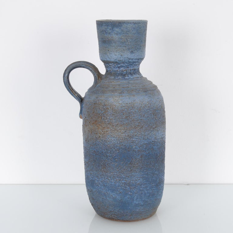 This ceramic vase was made in Germany, circa 1960. Its blue and gray glazed, textured surface and the stepped shoulder display the experimentation characteristic of West German pottery from this era. A circular handle sits on one shoulder.