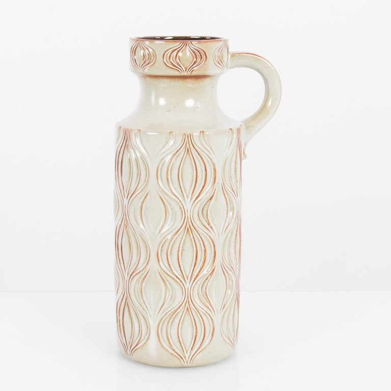 A ceramic vase from West Germany, circa 1960. An upright flask of white ceramic is decorated with a raised pattern, rippling and fluid, reminiscent of onion bulbs or tulips. The raised lines bear a soft tint of rosy orange, a warm shadow which