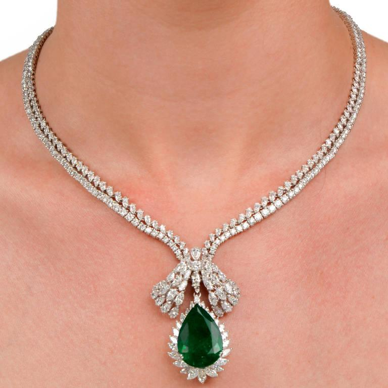 This artistically designed pendant necklace with distinctly cut diamonds and a prominent GIA Certified Genuine emerald is crafted in solid 18K white gold, weighing 68.5 grams and measuring 17.5