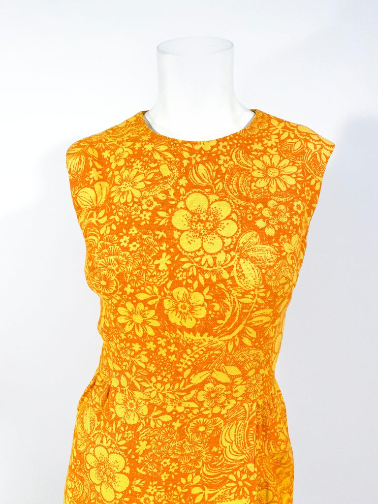 1960s day dress featuring a vibrant gold and orange floral print and a wrap around pleat skirt, and fitted waist. The metal zipper is located on the back of the dress.