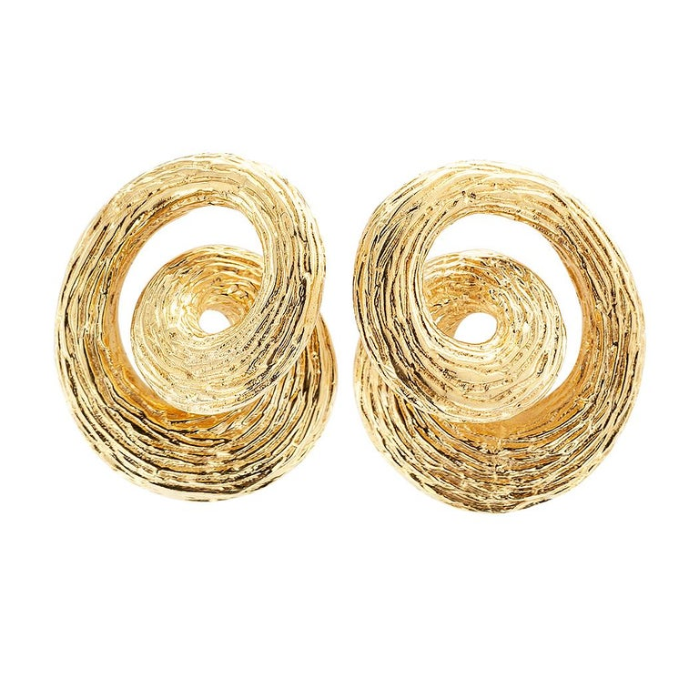 1960s gold knot ear clips. The matching designs resemble a circle that loops and curls on itself; thereby giving the impression of a knot, crated in 14-karat yellow gold finished with a bark like texture that is neither matte nor shiny. We love that