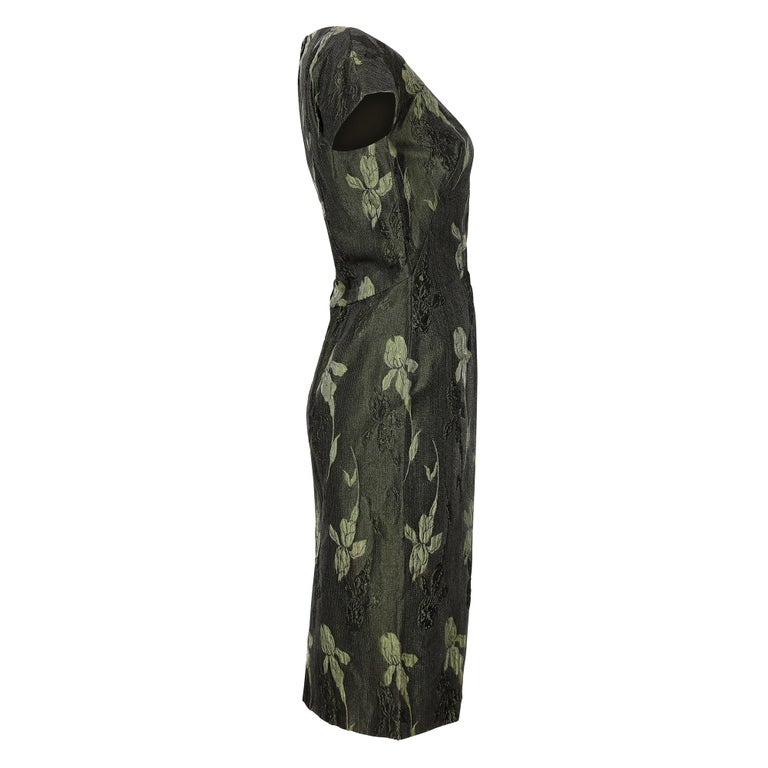 This elegant vintage 1960s metallic evening dress is of high-end, British manufactured quality although unlabelled. The opulent and textured brocade fabric has an iris design in alternating two-tone forest green which shimmers in the light with