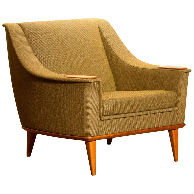 Beautiful and original midcentury lounge or easy chair with oak details by Folke Ohlsson for DUX, Sweden. This chair sits extremely comfortable and is in good condition.  Period: 1960. The dimensions are: Depth 77 cm, 30 inch, wide 77 cm, 30
