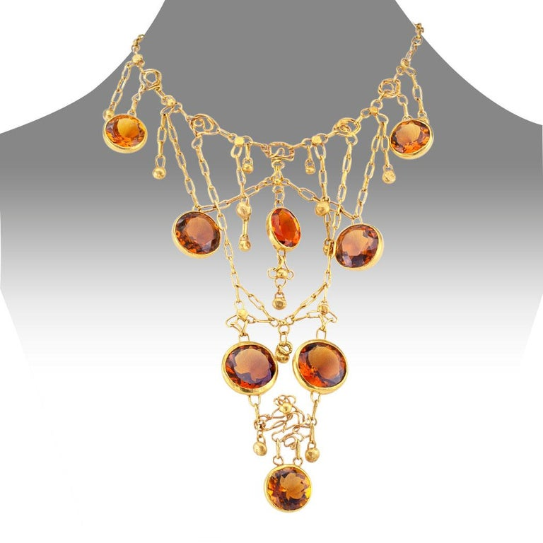 Madeira citrine and gold bib necklace circa 1960. The handcrafted design is decorated on the front by a cascading motif comprising an organic arrangement of gold wire work suspending a symmetrical array of small gold beads along with eight