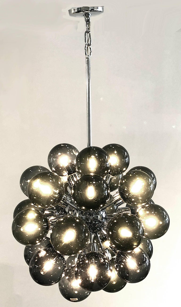 25 smoked glass globes cover the bulbs of this dramatic hanging Space Age light. Designed by Motoko Ishii for Staff Luechten, Germany. The frame and canopy are polished chrome. Measures: 40 H as shown. The diameter of the light portion is 25