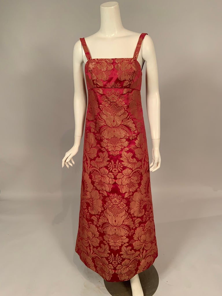 Helena Barbieri used a beautiful raspberry red silk with a woven metallic gold floral design for this chic 1960's dress and coat set. The dress has narrow straps an empire waistline and an elongated A line skirt. The boned bodice has a double zipper