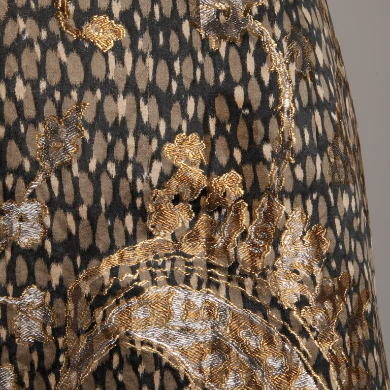 Absolutely stunning 1960s vintage silk satin cocktail dress by Helga. Metallic brocade paisley design over gray silk animal print. Nipped waist with bow detail. Stunning construction with a weighted bust and hand stitching throughout. Partially