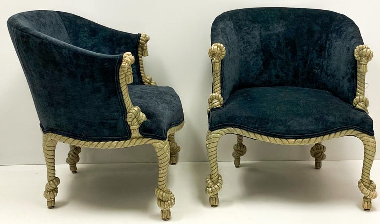 This is a pair of Hollywood Regency gilt and tassel pair of velvet tub chairs. The frames are gilt gesso over wood. The velvet is a recent addition. They are unmarked and in very good condition.