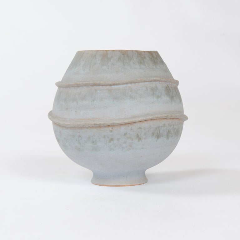 A footed vessel with muted celadon matte glaze accentuated by two undulating circular appliques, with contrasting high gloss glazed interior. Signed