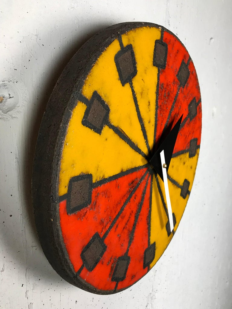 Eye-catching modernist Italian ceramic wall clock by Bitossi (Italian potter) manufactured by Howard Miller using hands designed by George Nelson (American designer). This desirable glaze has brilliant red and orange colors and a sgraffito technique