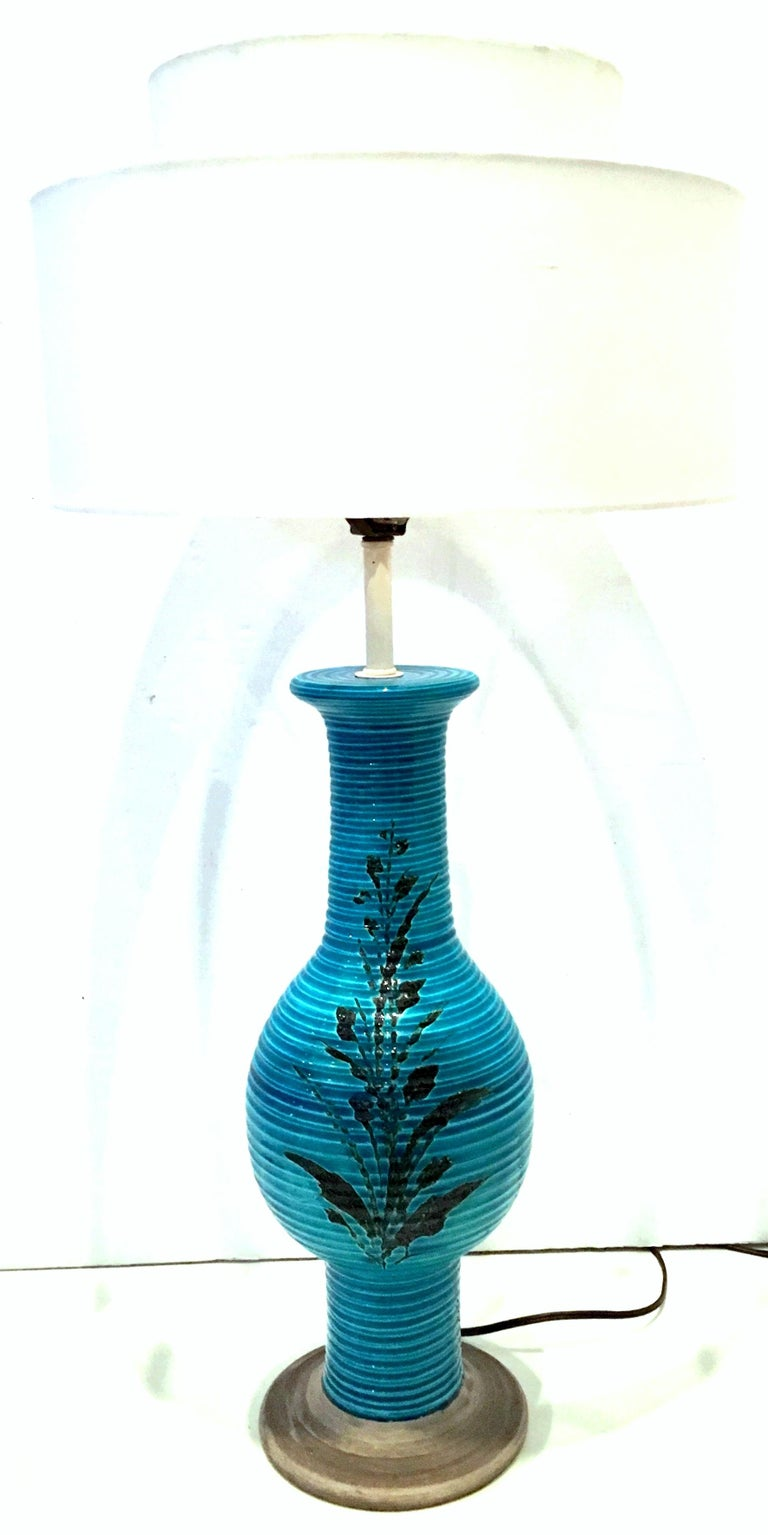 1960s Bitossi for Raymor Coveted Italian handcrafted, two-tone cerulean blue and black hand painted, double sided floral motif ceramic pottery lamp signed and numbered. The faux bois finished base is made of ceramic. The neck and socket, harp and
