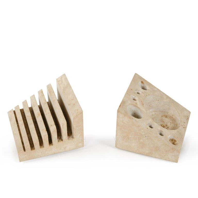 Enzo Mari's clever solution to the desk accessory question. Combining letter or note paper holder, pencil/pen holder, paper clip miscellany well, and bookends (dubbed Malta and Montecristo) executed in polished travertine. Works exceptionally well