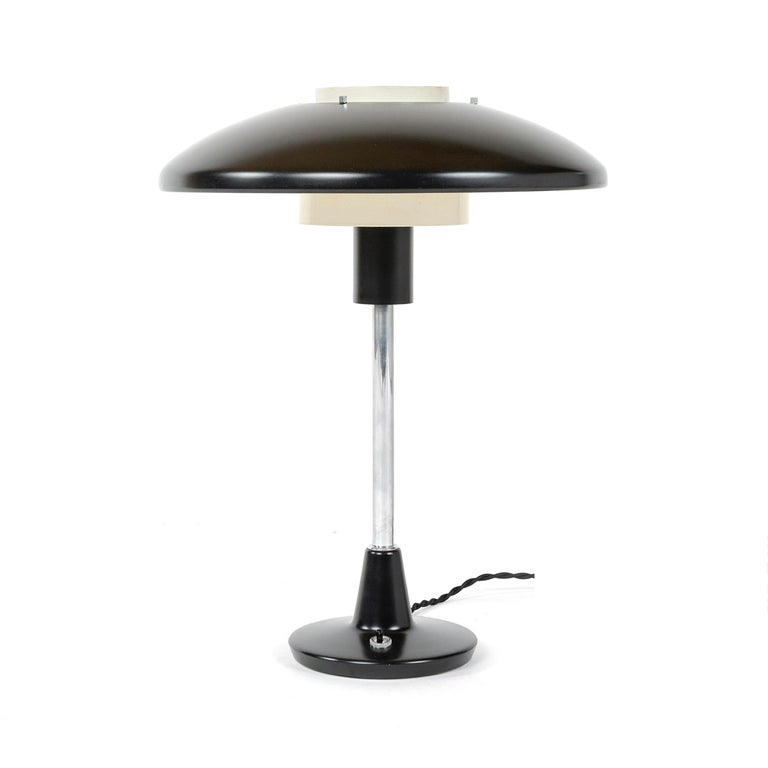 An elegant table or desk lamp with black-enameled spun metal shade providing a blanket of task light with an off-white-enameled inner core for up-light stemming from a black-enameled weighted base with a tactile flip switch.