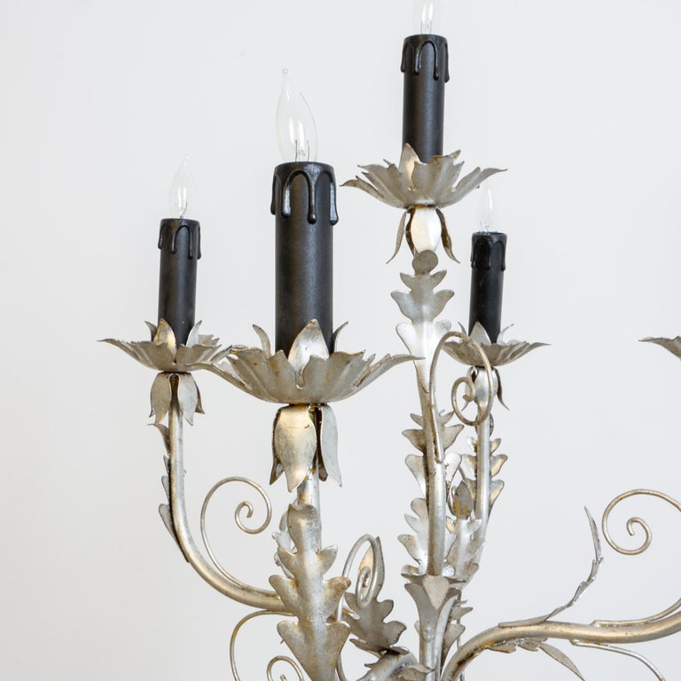 A metal lamp from Italy, circa 1960. Gold paint gilded, a unique decorative motif combines classical Italian flair with 1970s sensibility. A floral lamp base rests lightly in cherub arms, fitted with modern electrical wiring.