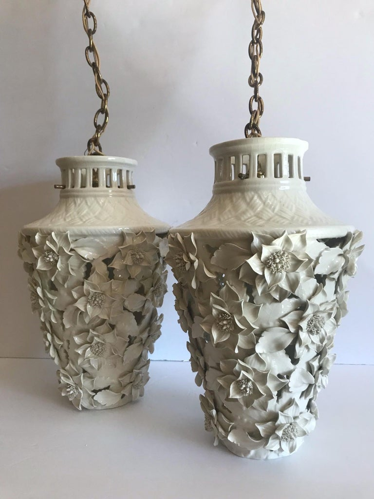 Pair of stunning Italian Blanc de Chine porcelain pendant chandeliers with exquisite floral details. The pendants have pagoda forms with etched bamboo design along the top with intricate handcrafted leaf and flowers throughout. Fitted with one light