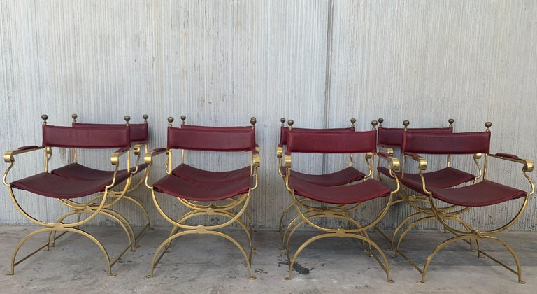 Set of eight beautiful 1980s Italian chrome gold and red leather Savonarola director's chair in perfect conditions, with very minor fading and great timeless patina. Very comfortable armchair, quilted in back and seat. Size: Height to the arm