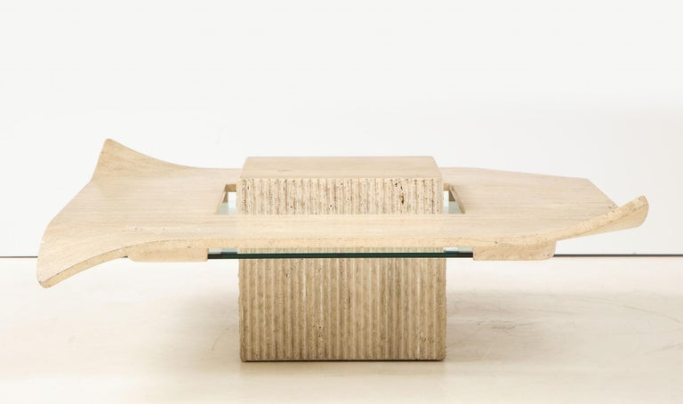 Gorgeous Italian Mid-Century Modern cocktail table. The carved base has a reeded stone detail in a rough finish. The polished travertine top has turned corners in a handerkerchief look reminiscent of the Willy Guhl style. The travertine top is
