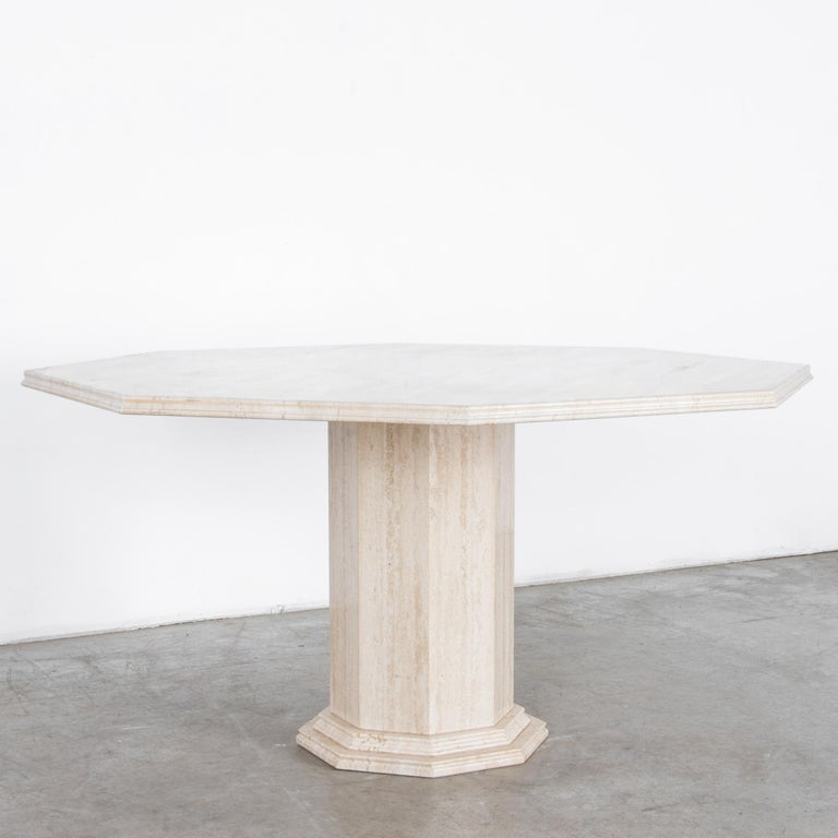 A cantilevered octagonal slab of light travertine rests on a faceted round pedestal, in this stylish and simple dining table. The tabletop is carved with an ogee edge profile, and framed below by a profiled column base, in a neoclassical inflected