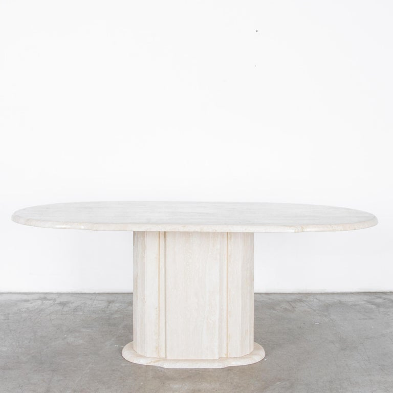 A cantilevered slab of light travertine rests on a faceted round base in this stylish and simple dining table. The tabletop is carved with rounded edge profile.