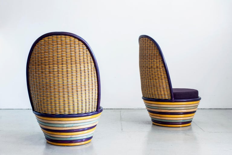 Vibrant pair of Italian woven wicker and rattan lounge chairs. Great colored striped rattan circular base and colored wicker back with newly upholstered purple cushioned seats.