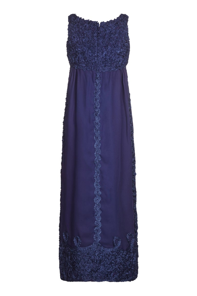 This attractive Jean Varon 1960s Midnight Blue evening gown is a sophisticated departure from the designer's trademark space-age style pieces, and has a softer, more feminine focus. The dress is sleeveless, with a classic Empire-Line cut that falls