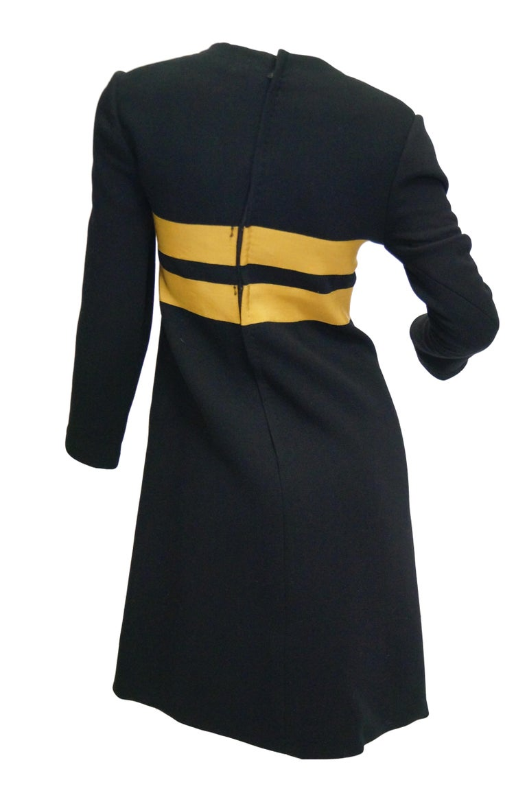 Wonderfully Mod dress created by Jeanne Lanvin and executed  with authorization by Maria Carine.  The black wool dress has a loose shift silhouette, jewel neckline, long sleeves, and falls just above the knee. The bust of the dress features two