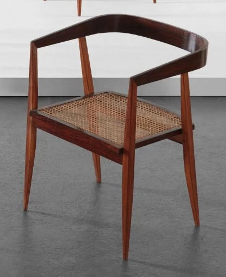 Ships from New York, NY. Set of nine 1960s Brazilian jacaranda dining chairs with curved back by Joaquim Tenreiro. Chairs have cane seat and measure 22 1/2 x 21 x 29 1/2 high. Chair shown on page 120 of Tenreiro book published by Icatu.   Ships from