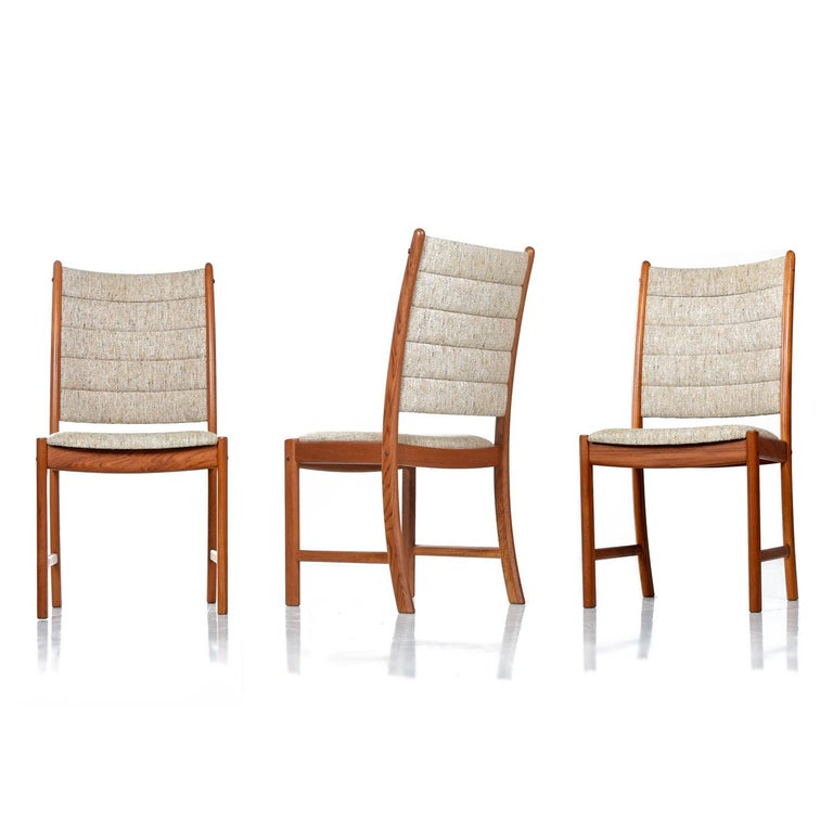A set of six solid teak dining chairs by Johannes Andersen for Uldum Møbelfabrik. The several decades old solid teak has a rich amber patina that bounces beautifully against the original wool fabric. The high back profile features four rows of