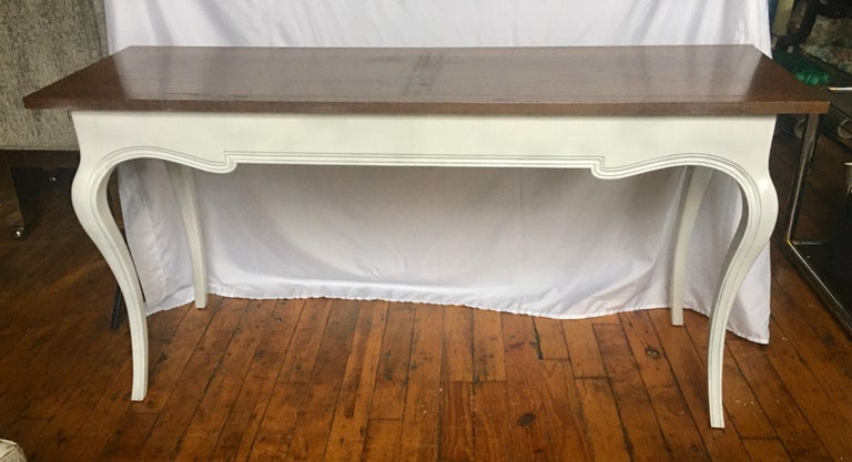 Midcentury French Provincial style console sofa table by John Stuart. Base features a white painted finish with curved cabriole legs and one single drawer. Top is stained wood. Table could also be used as a long desk.
