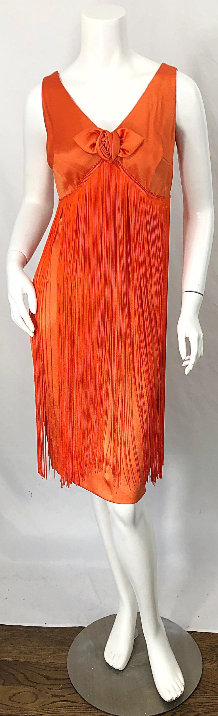 Beautiful vintage 1960s JOSEPH MAGNIN bright neon orange fully fringed flapper dress ! Features the perfect color orange, with hundreds of strands of Fringe throughout the entire dress. Hidden metal zipper up the back with hook-and-eye closure.