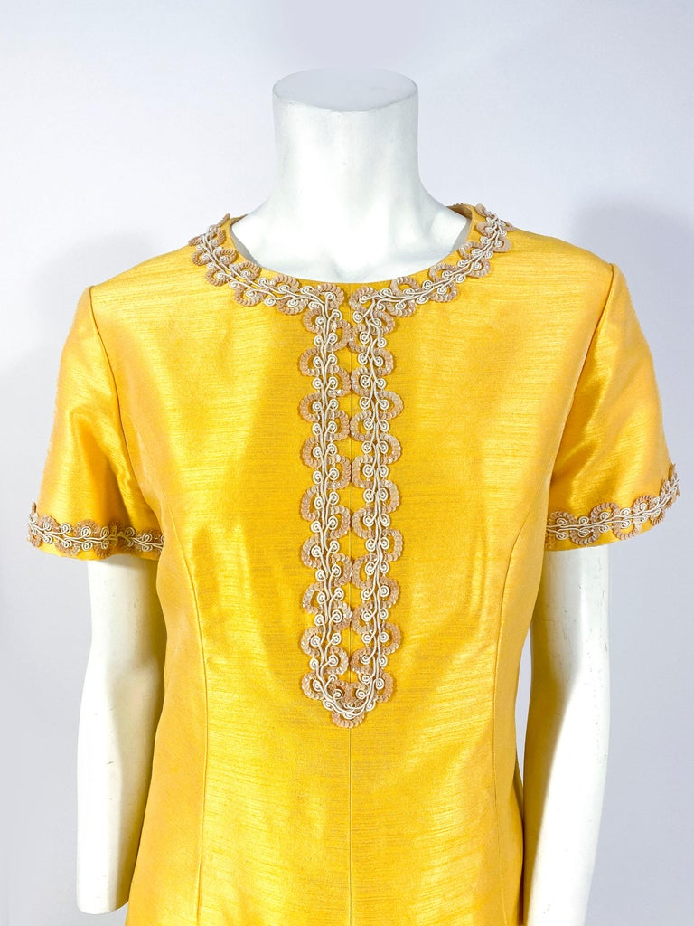 1960s Joseph Magnin Gold/yellow A-line dress with short sleeves and sequin/cord trim along the neckline, down the center, and on the sleeves. There are enlarged post darts to provide shape to the body of the dress and the back has the metal zipper