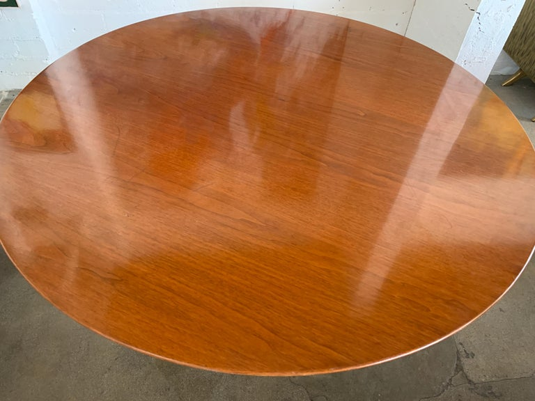 A vintage knoll Saarinen tulip table with a walnut top. It bears a vintage Knoll label that dates it to the 1960s as the address reads 320 Park Avenue. It is 54 inches in diameter and 28.25 inches tall. The top is quite lovely with age appropriate