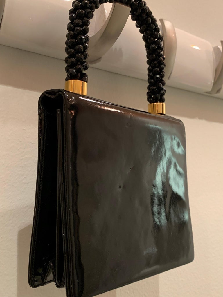 A smart 1960s Mod Koret handbag in genuine black patent leather. Handle is wrapped and covered entirely in black resin faceted beads. Snap flap closure.  inside pocket.   Bag measures 6